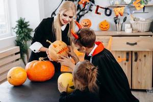 mãe e filhos segurando abóbora e ter momentos engraçados em casa. - conceito de Halloween foto