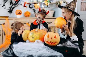 família tem momentos engraçados em casa. mãe e filha vão morder uma abóbora - conceito de Halloween foto