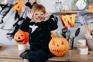 menina engraçada sentada ao lado da abóbora e mostrando um gesto assustador. - conceito de halloween foto