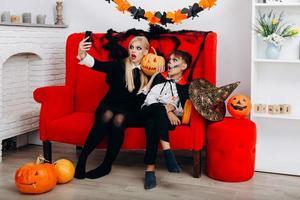 mulher e filho se divertem no sofá vermelho e fazem uma selfie. emoção e conceito de halloween foto