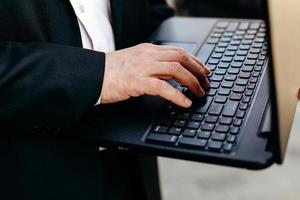 recortando a imagem do empresário sênior segurando o laptop na mão e digitando em close-up. foto