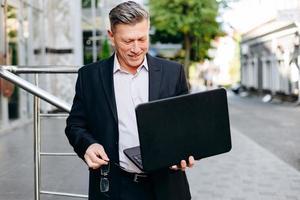feliz empresário sênior segurando laptop na mão na cidade ao ar livre e olhando para a tela. foto