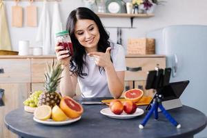 atraente, atlética, sorridente, jovem comendo alimentos saudáveis e preparando smoothies de frutas foto