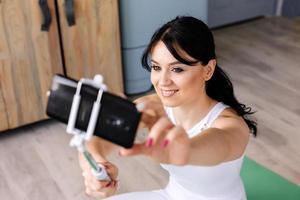 garota sorridente é fotografada em seu smartphone foto