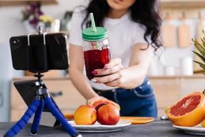 jovem feliz preparando um saboroso smoothie nutritivo foto