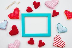 corações multicoloridos e uma moldura de azul são espalhados sobre um fundo branco. tema para o dia dos namorados. lugar para texto foto