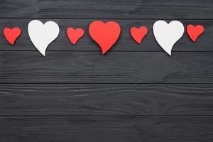 corações vermelhos e brancos em fundo escuro de madeira. foto