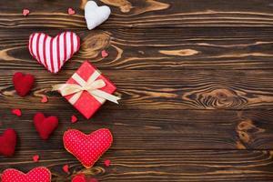 tema de amor, corações têxteis dispostos em uma superfície de madeira, uma caixa de presente para o dia dos namorados foto