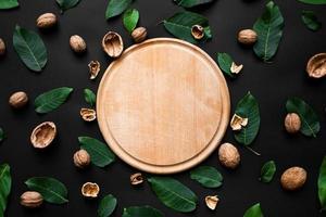 casca de noz e folhas verdes frescas espalhadas em um fundo preto. tábua de madeira no centro foto
