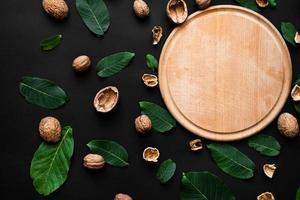casca de noz e folhas verdes frescas espalhadas em um fundo preto. tábua de corte de madeira do lado direito foto