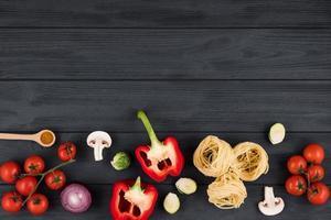 vista superior na mesa de madeira com produtos italianos, pimentas, tomates, massas. copie o espaço para o texto. foto