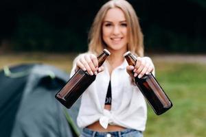 mulher em pé e segurando uma cerveja no acampamento. retrato de close foto