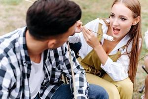 garota closeup comendo uma comida grelhada e olhando para o homem no acampamento foto