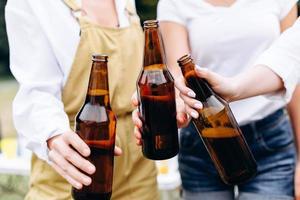 uma companhia de amigos levantando uma garrafa - closeup mãos foto