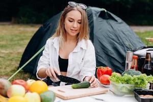 mulher preparando comida ao ar livre no acampamento foto