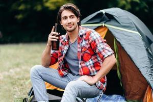 um cara segurando uma garrafa de cerveja e sorrindo, olhando para fora. tenda no fundo foto