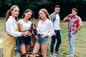 uma companhia de amigos levantando uma garrafa com uma cerveja no acampamento. - imagem horizontal foto