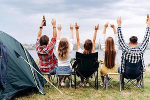 uma companhia de amigos almoça no acampamento. eles levantam as mãos. - vista traseira foto