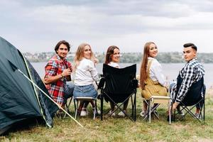 uma companhia de amigos se divertem no acampamento. eles sentam meia volta. - vista traseira foto