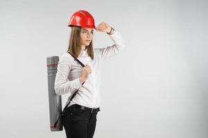 arquiteta mulher fica com um tubo nas costas toca o capacete laranja na cabeça. - imagem horizontal foto