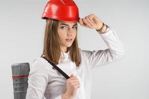 closeup retrato de arquiteto de mulher bonita fica com um tubo nas costas toca o capacete laranja em sua cabeça. - imagem horizontal foto
