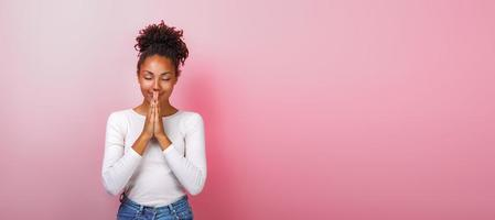 retrato de mulher em pose de súplica com sorriso e olhos fechados sobre fundo rosa. copyspace foto
