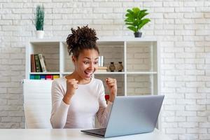 Mulher afro-americana feliz grita fazendo um gesto de vencedor com os punhos cerrados foto