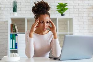 mulher tem uma dor de cabeça crônica, tocando as têmporas para aliviar a dor durante o trabalho no laptop foto