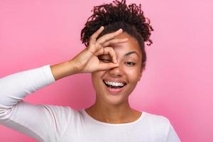 retrato de uma garota engraçada fazendo um gesto ok com os dedos e olhando através dele closeup - imagem foto