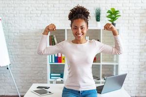 mulher afro-americana feliz faz um gesto mostrando o bíceps como um atleta. - imagem foto