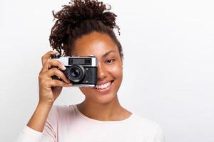 Feche o retrato de uma garota viajante feliz com uma câmera fotográfica na mão e olhando para ela - imagem foto