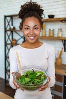 linda mulher em casa mostrando comida saudável, tem nas mãos uma salada - imagem foto