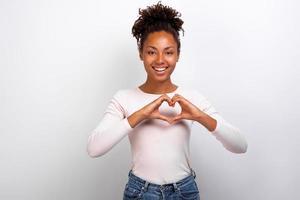 mulata bonita mostra um gesto de coração com os dedos próximos ao peito. gesto de conceito - imagem foto