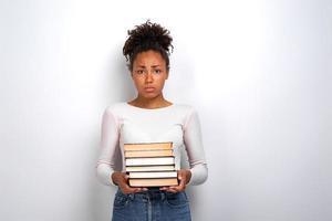 triste jovem infeliz segurando livros em pé no fundo branco do estúdio. de volta à escola foto