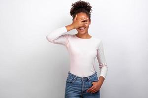 mulher fechou os olhos com o braço e olhou divertidamente por entre os dedos em pé no estúdio - imagem foto