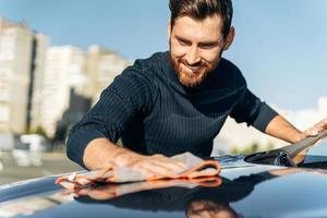 vista recortada do homem barbudo com um lenço de microfibra cinza polindo seu novo carro elétrico. bonito homem caucasiano lavando e limpando seu carro com sorriso de prazer. conceito de lavagem de carro foto