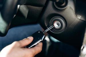 o foco seletivo da mão masculina fecha a chave de ignição do carro, a direção do carro e o painel. conceito de viagens e transporte foto