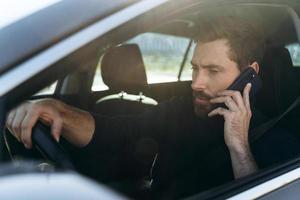 vista da rua para o homem caucasiano concentrado olhando para a janela enquanto conversa via smartphone com seu colega durante o longo caminho para o trabalho foto
