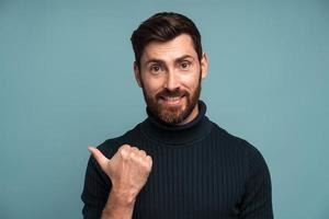 olhe aqui. retrato de homem moreno amigável positivo com barba em pé e apontando para o espaço vazio, esquerdo para texto, anuncie. estúdio interno tiro isolado em fundo azul foto