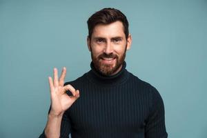 tudo está bem. chefe barbudo satisfeito mostrando o gesto ok com os dedos, aprovando o trabalho, satisfeito com a qualidade. estúdio interno tiro isolado em fundo azul foto