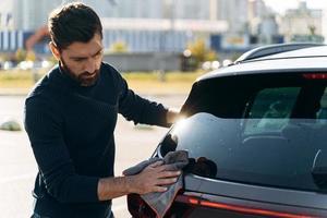 cintura para cima vista do retrato de um homem concentrado e satisfeito limpando a parte de trás de seu carro novo, enquanto passava um tempo na rua durante o dia ensolarado de verão. foto