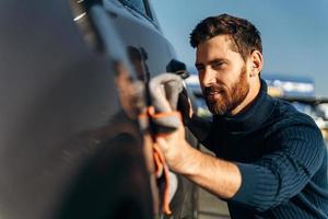 homem limpando o carro na rua. lavagem de detalhamento do carro durante o dia ensolarado. bonito homem barbudo em roupa casual lavando portas e capô do carro com pano de microfibra foto