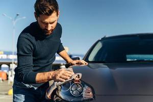 jovem bonito homem caucasiano lavando e limpando seu carro preto moderno ao ar livre. homem barbudo com um lenço de microfibra cinza polindo seu novo carro elétrico. conceito de lavagem de carro foto