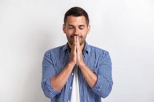 closeup retrato de homem bonito faz um gesto de oração. - gesto de conceito foto