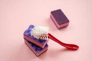 escova doméstica e esponja de cozinha deitada sobre fundo rosa foto