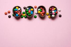 sobrecarga de Páscoa feliz com ovos de Páscoa de chocolate e decorações em um fundo rosa com espaço de cópia. foto