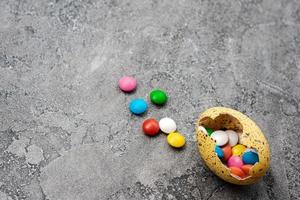 ovos de páscoa com doces sobre fundo cinza foto