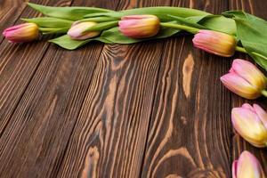 tulipas nas tábuas de madeira da mesa. cartão para o dia das mães, a Páscoa. copie o espaço foto