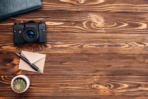 em uma mesa de madeira encontra-se uma câmera, um caderno, um cacto. copie o espaço foto