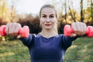 bela jovem trabalhando exercícios com halteres, como parte de seu estilo de vida. foto